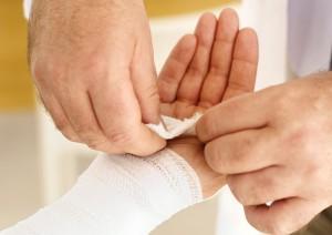 Helfende Hände verbinden den Arm des Patienten mit einem Verband.